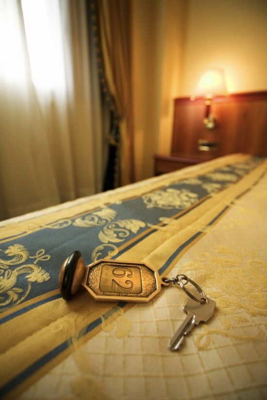 Hotel Room Key Atop the Bed